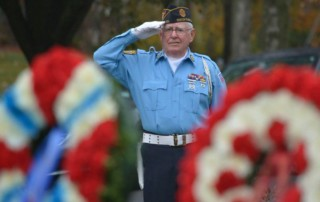American Legion color guard captain Thomas Keane, a Marine Corps veteran of the Vietnam era, delivers a salute as Taps are played during Veterans' Day ceremonies in Fanwood, NJ, Wednesday, Nov. 11, 2015